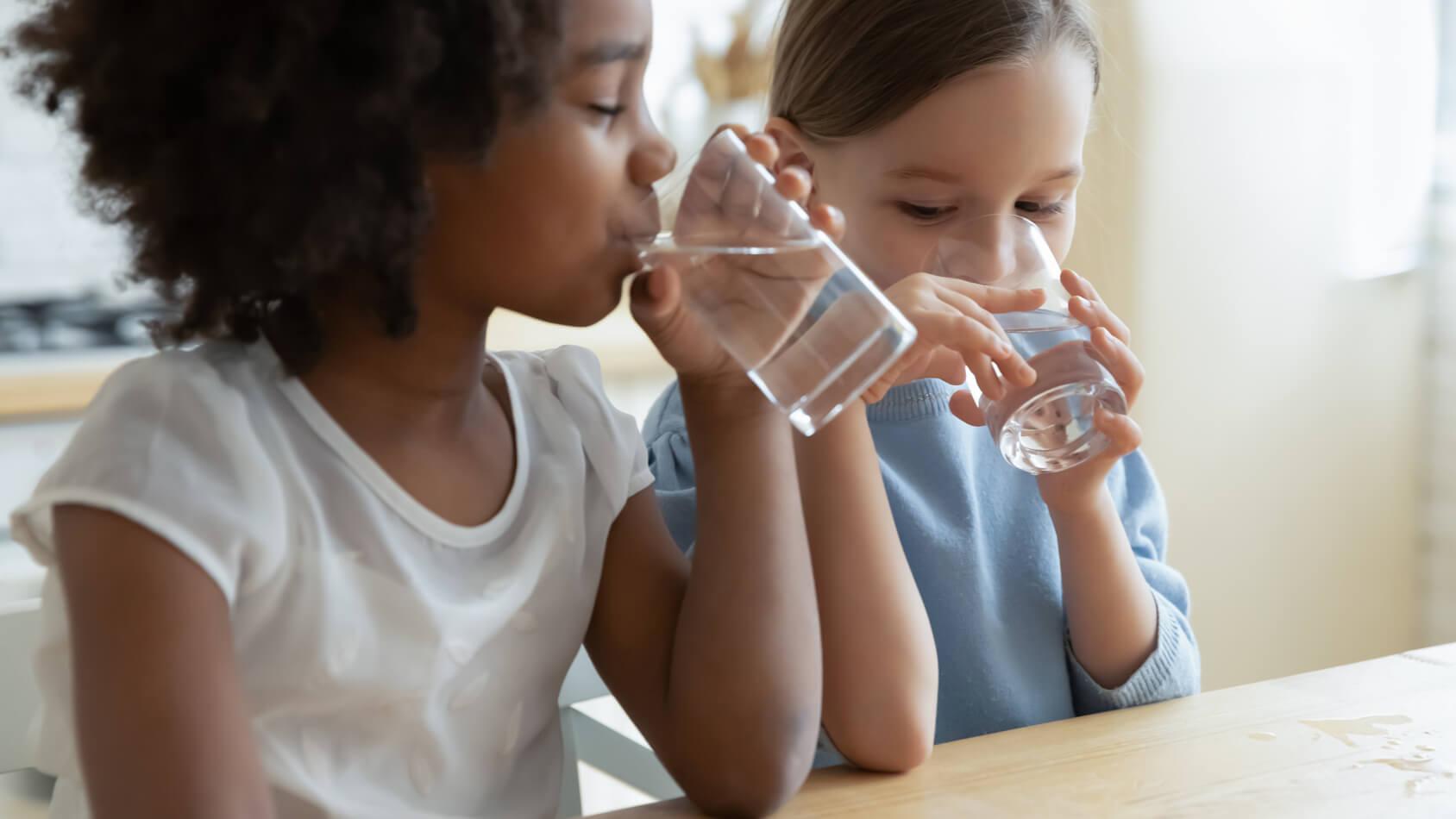 Two children drinking water
